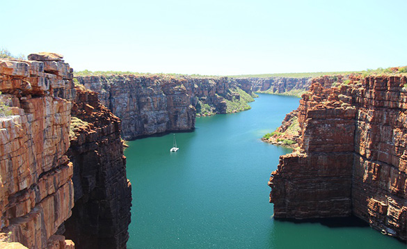 boat sailing along a wide turquoise blue river meandering through red craggy cliffs/