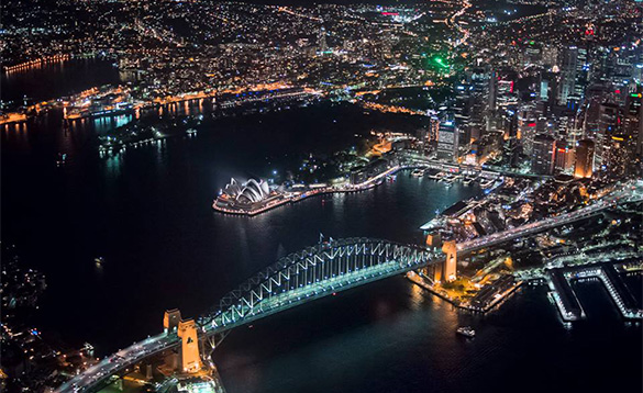 aerial photograph of city lights of Sydney at night with bridge and opera house lit up/
