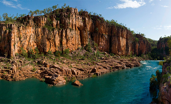 fast flowing turquoise river at the foot of russet coloured craggy cliffs/