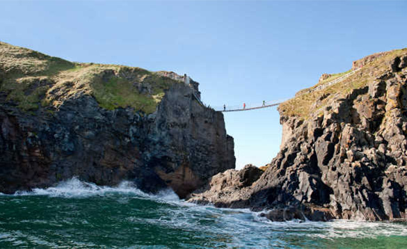 People walking across the Carrick-a-rede rope bridge above waves breaking against the cliffs/