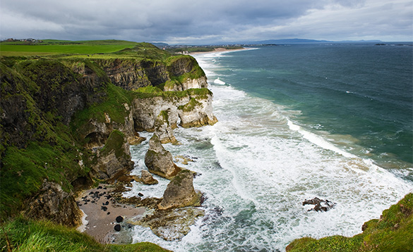 Waves breaking against cliffs onto a sandy beach along the Antrim coast in Northern Ireland/