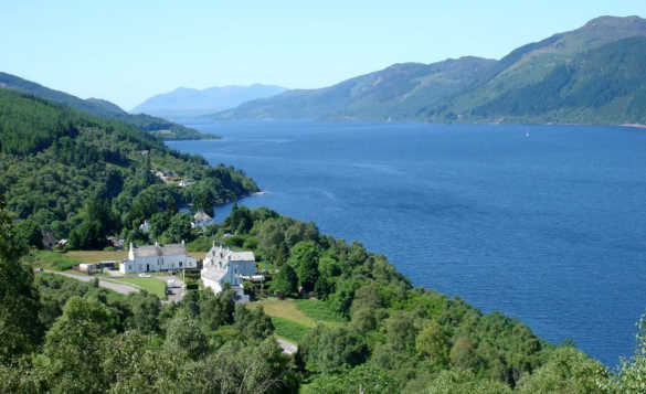 White houses set amongst trees on the shore of Loch Ness/