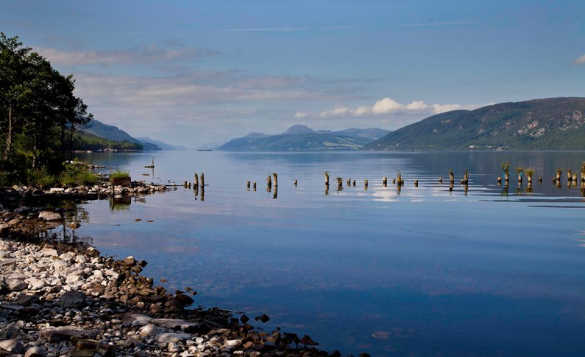 View from a pebbly shoreline across Loch Ness to hills in the distance/