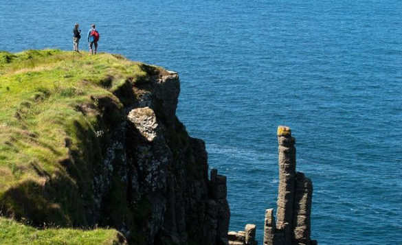 Couple standing on a grassy cliff top looking out to sea/