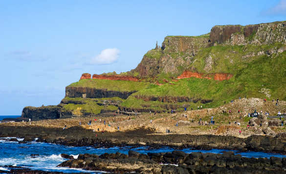 People exploring the rocks and pillars of the Giant's Causeway /