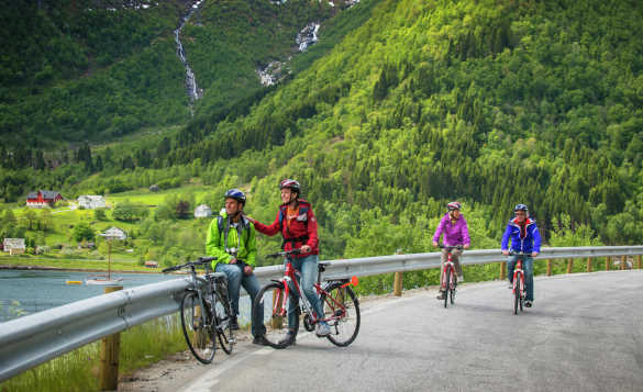 Two couples riding bicycles and enjoying the views of tree covered moutains with cascading waterfalls in Norway/