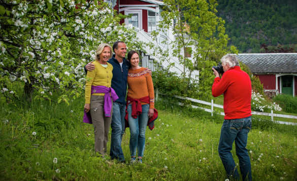 Two ladies and a man having their photograph taken whilst standing in front of a tree in blossom/