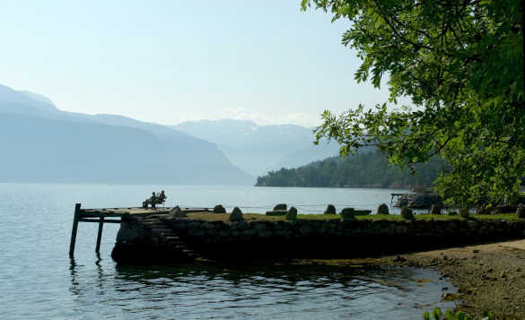 Couple sitting on a seat admiring the views across Sognefjord in Norway/