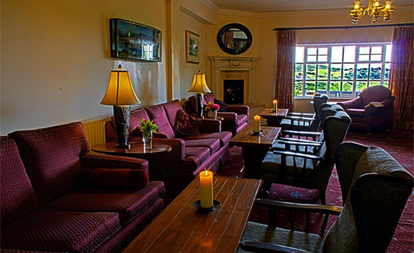 Bar area at the Abbeyglen Castle Hotel with chairs arranged around tables./