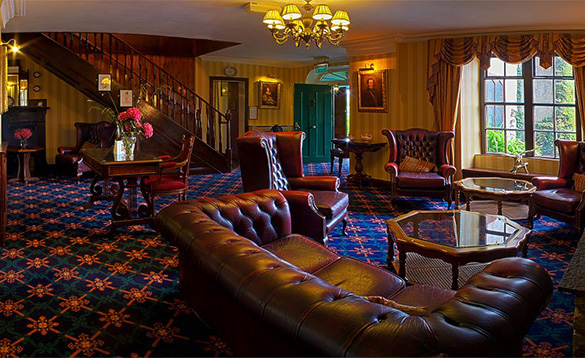 Lounge at the Abbeyglen Castle Hotel with leather Chesterfield suite and high back red leather chairs arranged around glass coffee tables./