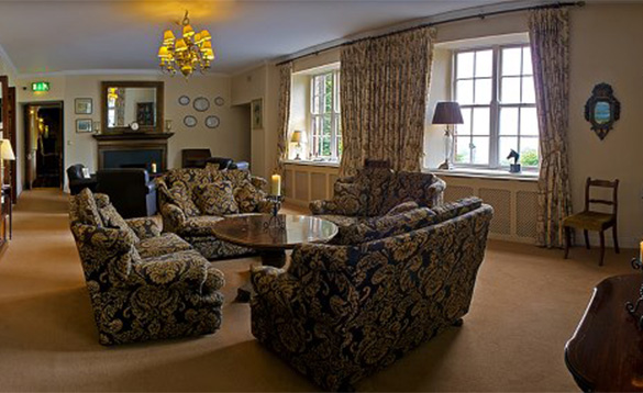 Lounge at the Abbeyglen Castle Hotel with settees arranged around a wooden table/