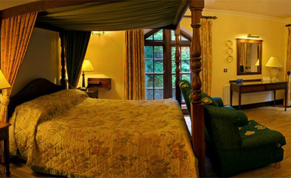 Bedroom at the Abbeyglen Castle Hotel with large four poster bed/