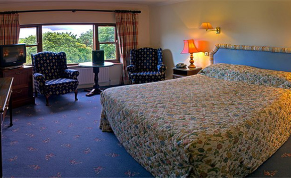 Bedroom at the Abbeyglen Castle Hotel with large double bed and two chairs and table in front of the window/
