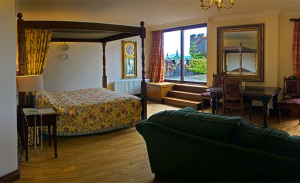 Bedroom at the Abbeyglen Castle Hotel with large four poster bed and three steps leading to courtyard/