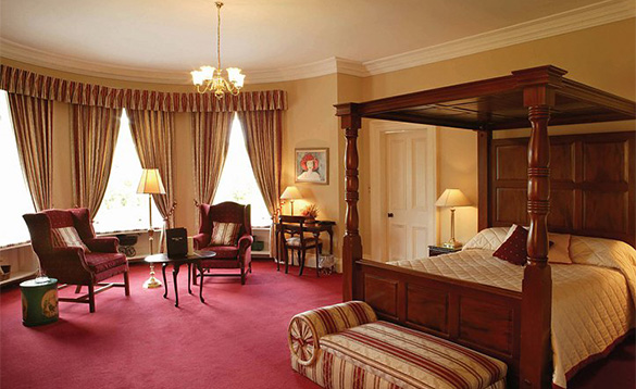 Bedroom at Ballyseede Castle Hotel with four poster bed and two chairs in a bay window/