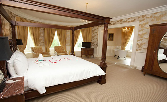 Bedroom at Ballyseede Castle Hotel with large four poster bed and roll top bath tub in separate area/