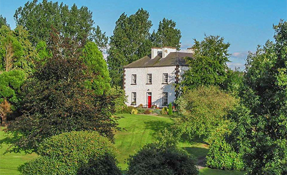 two storey farmhouse with red front door situated amongst trees and bushes/