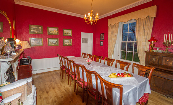 dining room with red painted walls and pine floor boards and large table in the middle of the room with six chairs down either side/