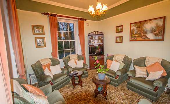 lounge in a B&B with pale green soafs and chairs with orange and cream cushions/