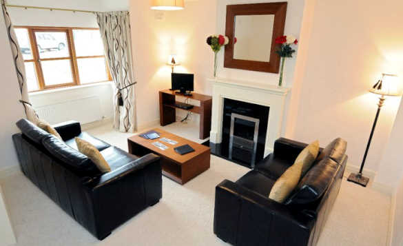 Lounge in a self-catering cottage at Kilronan Castle with two black leather sofas /