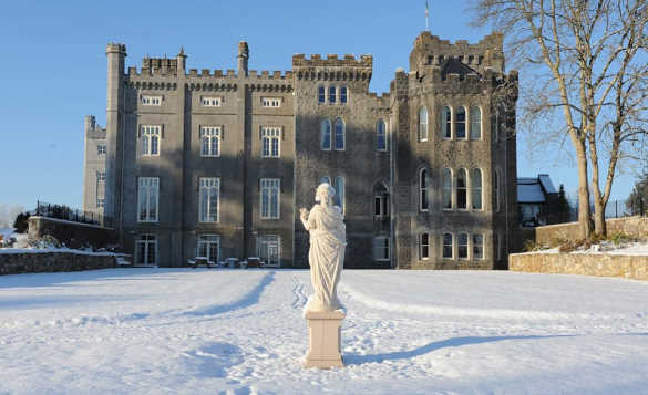 White statue beside snow covered lawns in the front of Kilronan Castle/