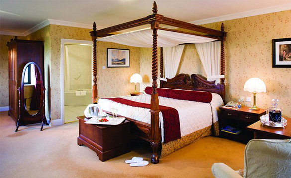Bedroom at the Knockranny House Hotel with four poster bed and tea tray with champagne/