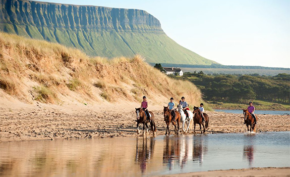 Group of people riding horses along the beach in Co Sligo/