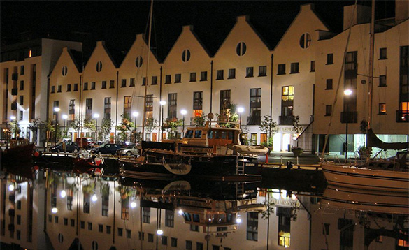 Night view of boats moored alongside buildings in Galway harbour/