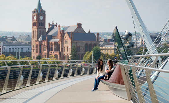 Couple of ladies sitting on a seat on the Peace Bridge in Londonderry with the city in the background/