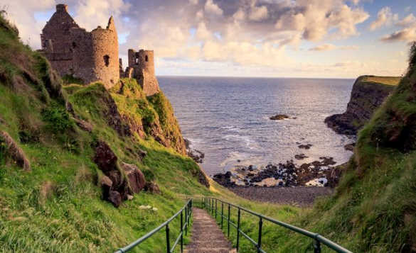 Path leading down a hill past Dunluce Castle to a rocky beach/