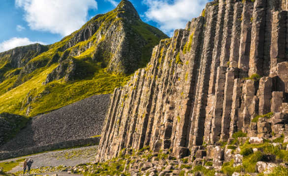 Two people looking at the large pillars of the Giant's Causeway/