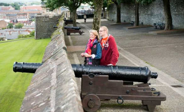 Couple standing next to a canon on the city wall of Derry/