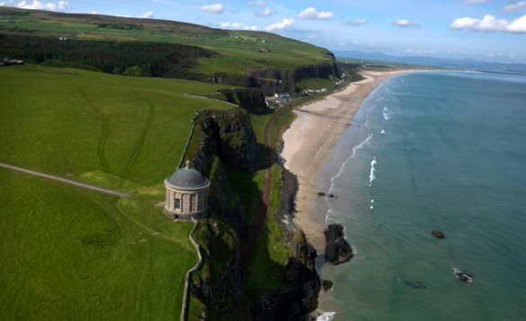 Mussenden Temple at the edge of grass covered cliffs above the sandy beach at Downhill Strand/
