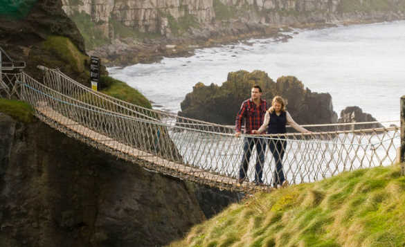 Couple crossing the Carrick-a-rede rope bridge/