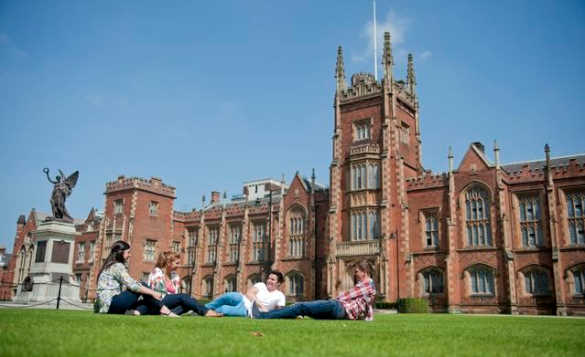 Group of people relaxing on the grass in front of Queens University, Belfast/