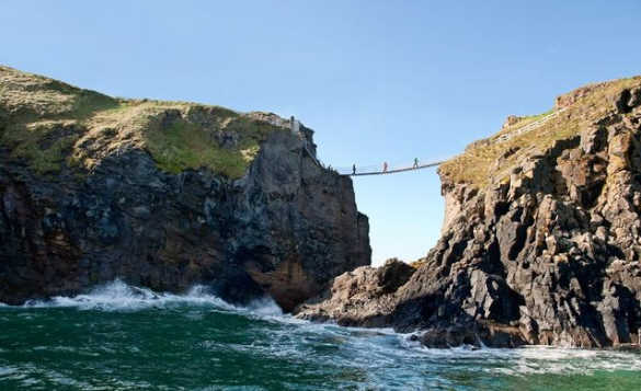 People walking across the Carrick-a-rede rope bridge suspended between two rocky cliffs with waves crashing at the bottom/
