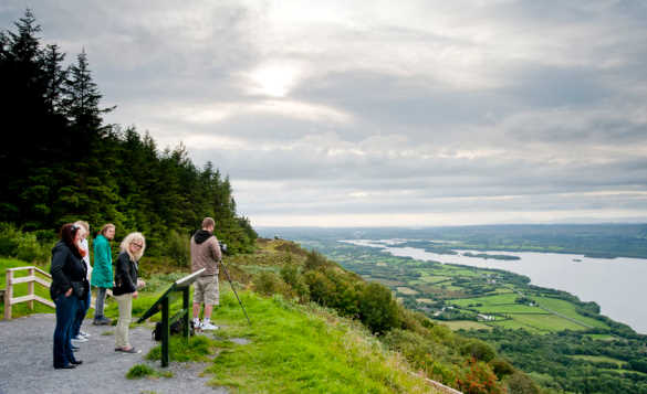 Group of people at Magho Viewpoint, Navar Forest Park, Co Fermanagh enjoying the view over open countryside and a large lough/