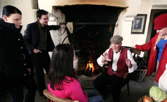 Group of tourists listening to the tales told by an old man sitting by an open fire in a cottage at the Ulster American Folk Park/