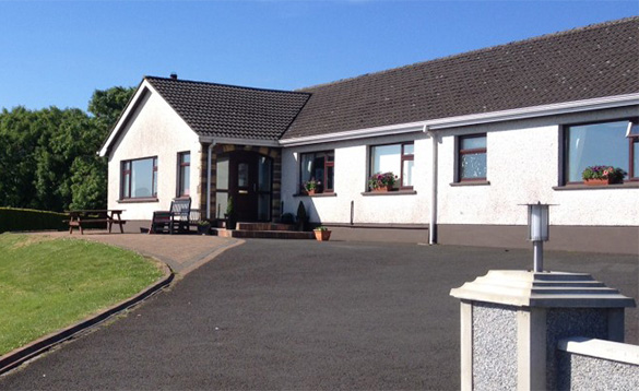 Driveway leading to a white bungalow and the entrance to Cullentra House, Cushendall/