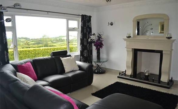 Lounge at Cullentra House, Cushendall with black leather corner settee and cream marble fireplace/