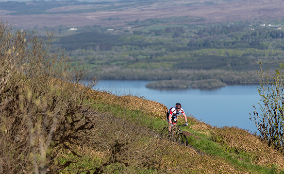 Cyclist biking across a hill beside Lough Erne/