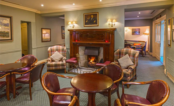Lounge at the Londonderry Arms Hotel, Co Antrim with tables and chairs set around an open fire/
