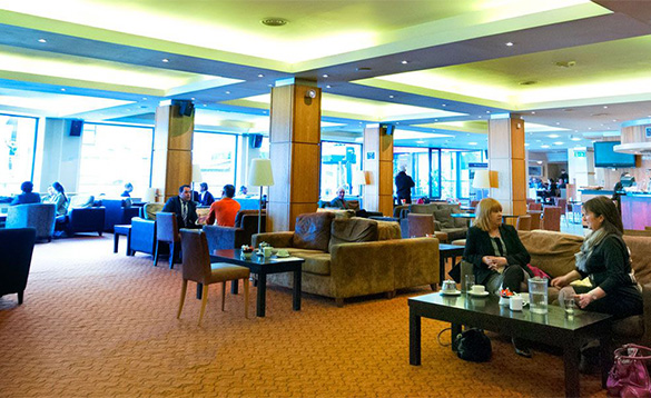 People enjoying drinks and chatting while sitting in the reception at the Wellington Park Hotel in Belfast/