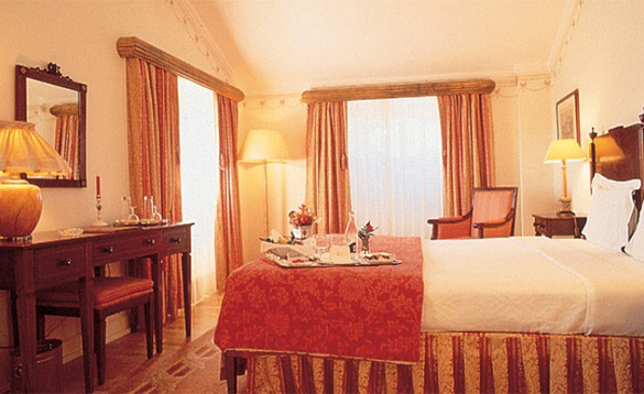 hotel bedroom with double bed with tray laid with fruit and drinks on top of it/