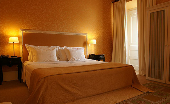 luxurious hotel bedroom with gold patterned wallpaper and double bed with gold throw/