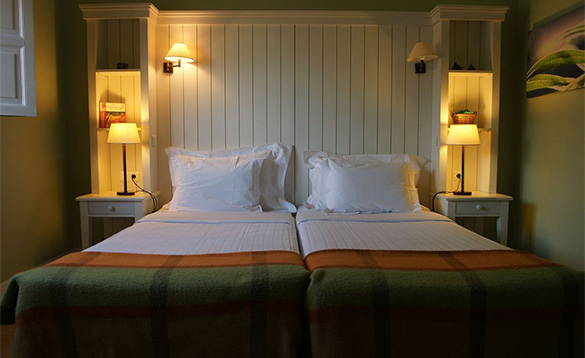 hotel bedroom with white wood panneling on walls and a two single beds pushed together to make a double/