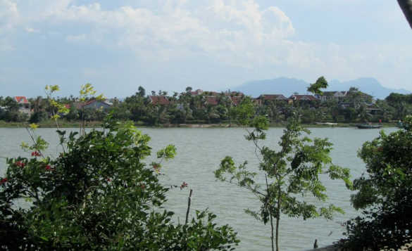 Green trees surrounding a lake of clear water with some houses visible in the far distance. /