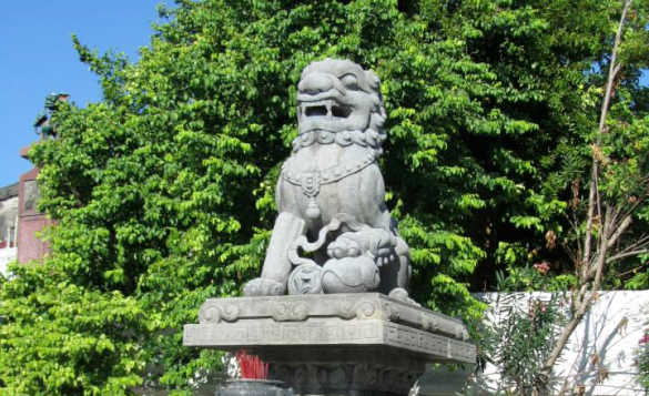 Grey lion statue with trees in the background./