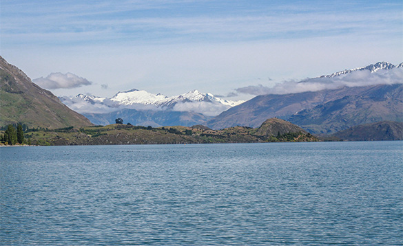 view across a lake to snow capped mountains/