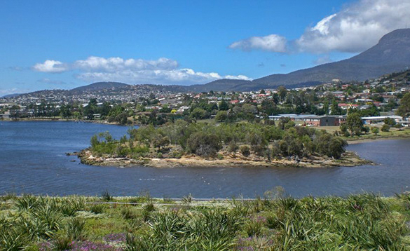 view across a wide river to a large sprawling town sitting at the foot of mountains/